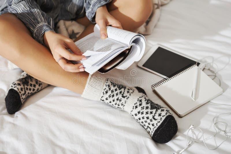 Het zijhoekschot van vrouwenzitting met gekruiste handen op bed, die buitensporige sokken, het maken dragen neemt van terwijl thu stock foto