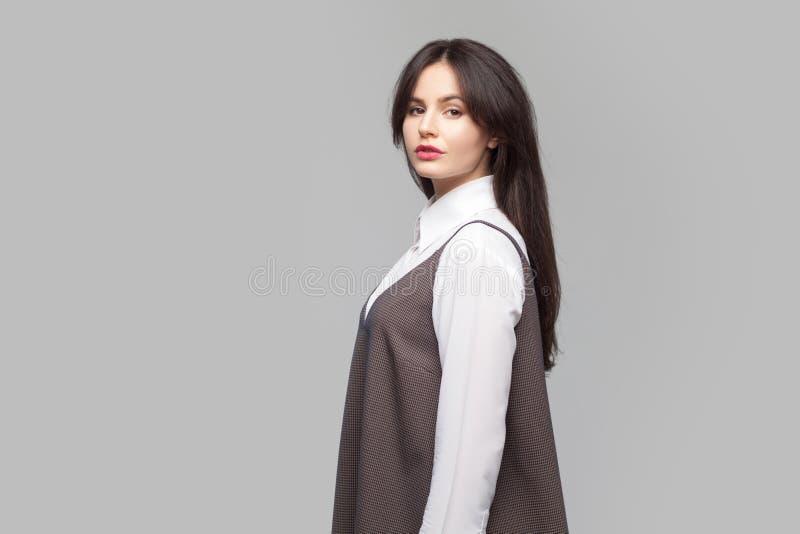 Het zijportret van de profielmening van ernstige mooie jonge vrouw in wit overhemd en bruine schort met make-up en donkerbruine h royalty-vrije stock foto
