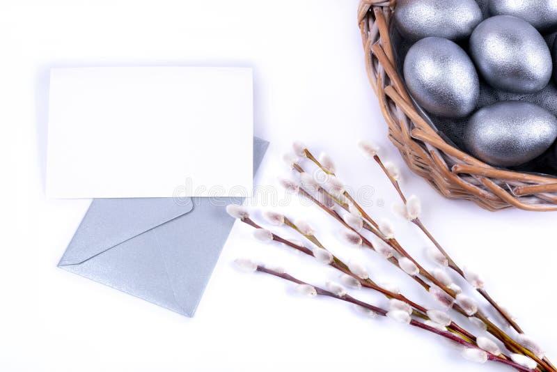 Het zilver kleurde paaseieren in rieten mand, de takken van wilgenkatjes, lege kaart op een zilveren envelop royalty-vrije stock fotografie
