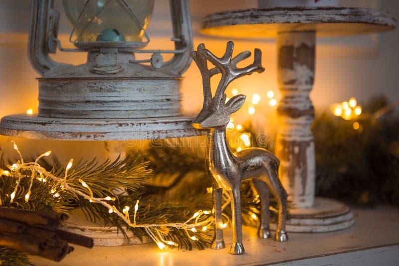 Het zilveren cijfer van de Kerstmisdecoratie van een hert, pijpjes kaneel in feestelijke gele lichtenslinger royalty-vrije stock fotografie