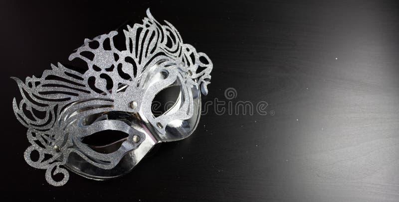 Het zilveren die masker van mardigras, op een Zwarte achtergrond wordt geplaatst royalty-vrije stock foto's