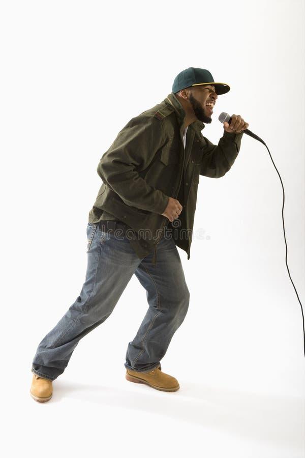 Het zingen van de mens in microfoon stock fotografie