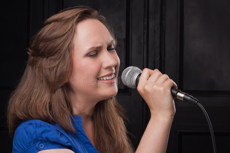 Het zingen van het meisje aan de microfoon in een studio stock afbeeldingen