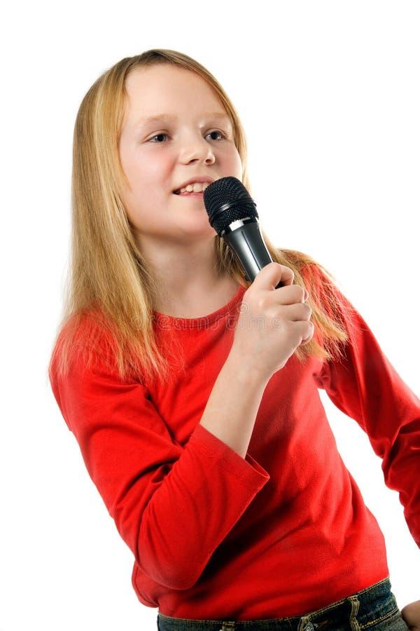 Het zingen van het meisje in microfoon over wit stock afbeeldingen