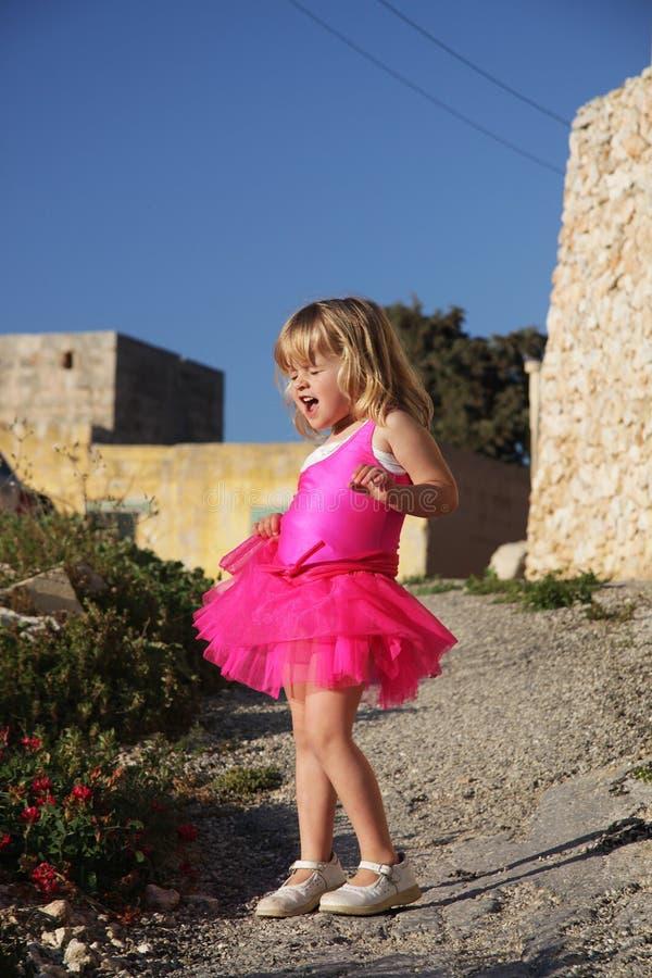 Het zingen van het meisje in roze balletkleding stock afbeeldingen