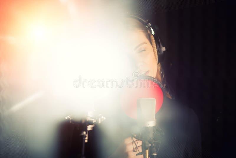 Het zingende meisje zingt aan de professionele microfoon in de verslagstudio Het proces van leidt tot een nieuw klaplied door jon stock afbeelding