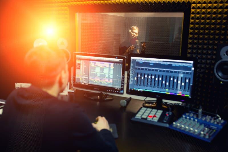 Het zingende meisje zingt aan de professionele microfoon in de verslagstudio Het proces van leidt tot een nieuw klaplied door jon royalty-vrije stock foto
