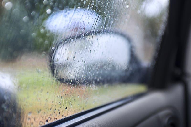 Het zitten in auto` s cabine terwijl buiten het regenen de regendaling is nog op het vensterglas royalty-vrije stock afbeeldingen