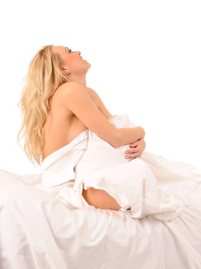 Het zitten in bed glimlachende vrouw royalty-vrije stock foto