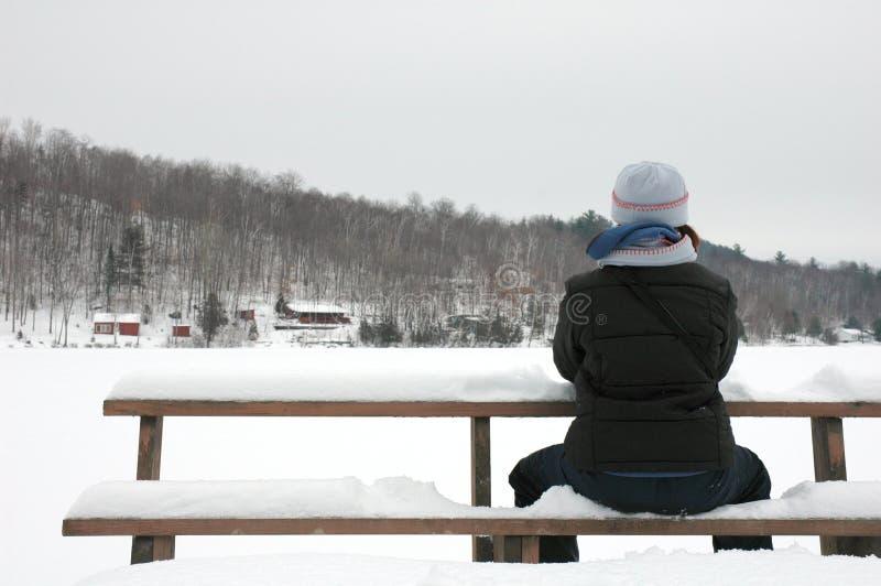 Het zitten in de sneeuw stock afbeeldingen