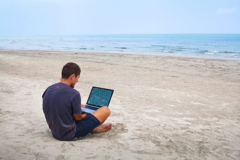 Het zitten met computer op het strand royalty-vrije stock afbeeldingen