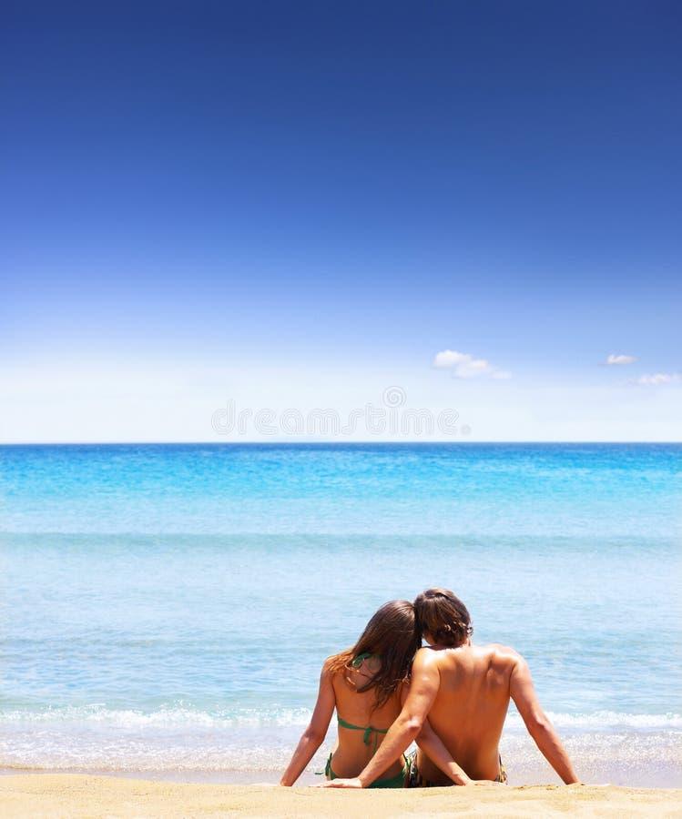 Het zitten op het strand stock foto's