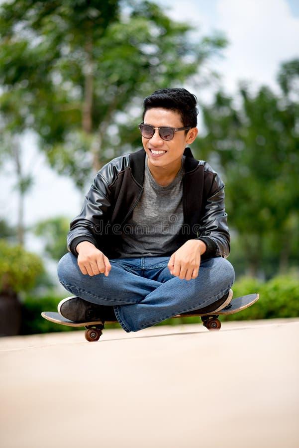 Het zitten op skateboard royalty-vrije stock afbeelding