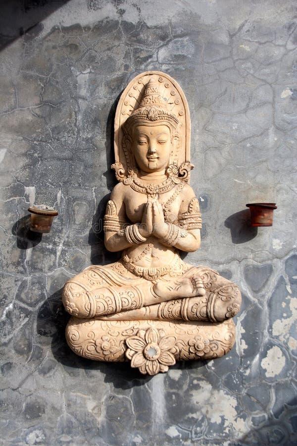 Het zitten van het bidden Boedha standbeeld op steenmuur met kleine kaarshouders royalty-vrije stock foto