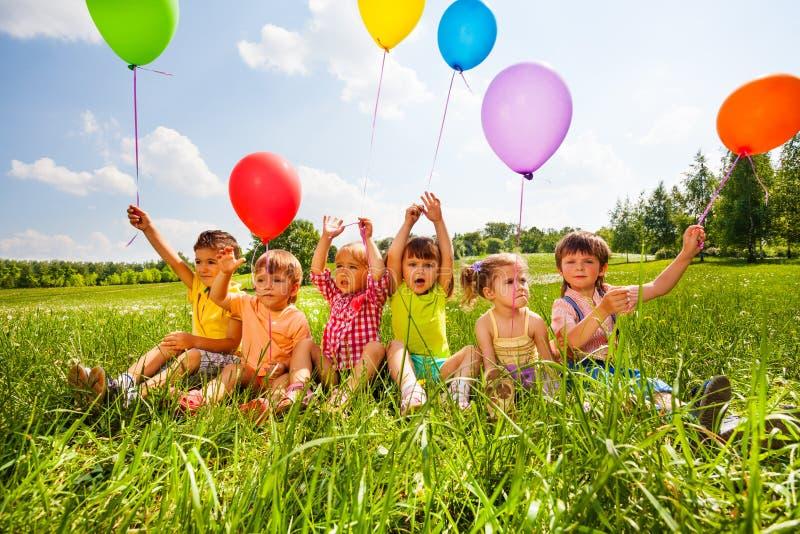 Het zitten van grappige jonge geitjes met ballons in de lucht stock fotografie