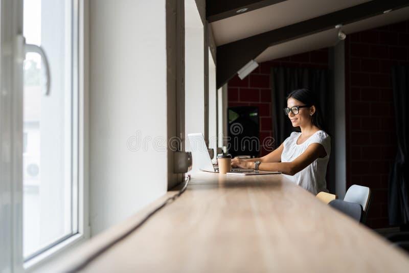 Het zoeken naar nieuwe oplossing Peinzende jonge mooie onderneemster in glazen die aan laptop werken terwijl het zitten bij haar stock foto