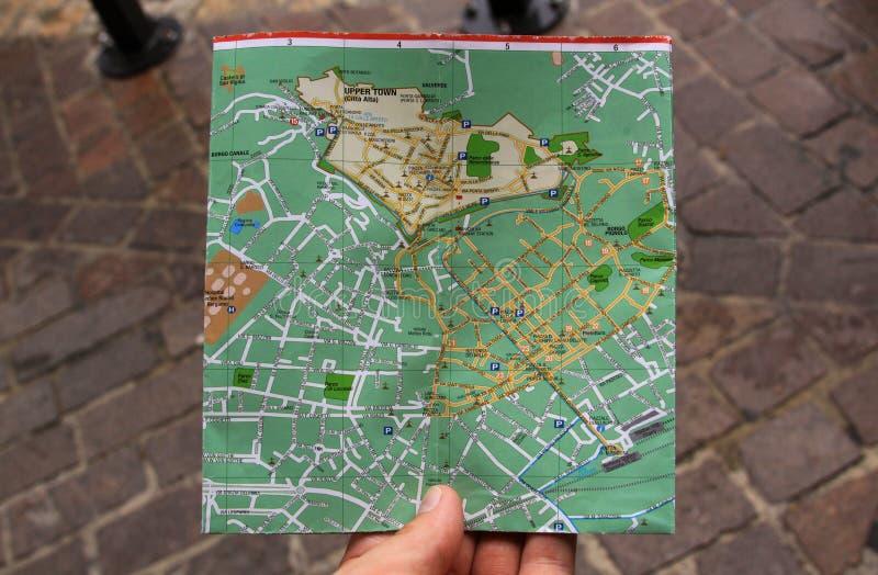 Het zoeken naar richtingen op een stadskaart met hand stock foto