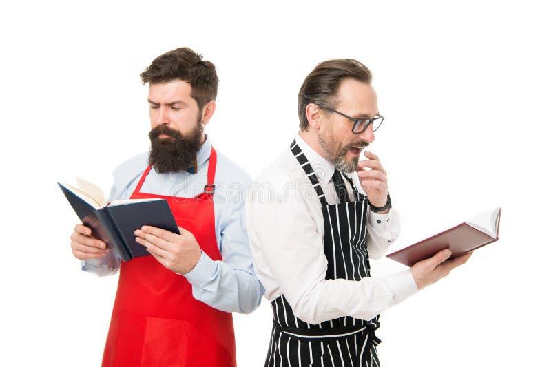 Het zoeken van beter recept Verbeter het koken vaardigheid Boekrecepten Volgens recept Mensen gebaarde chef-koks met boeken of stock foto