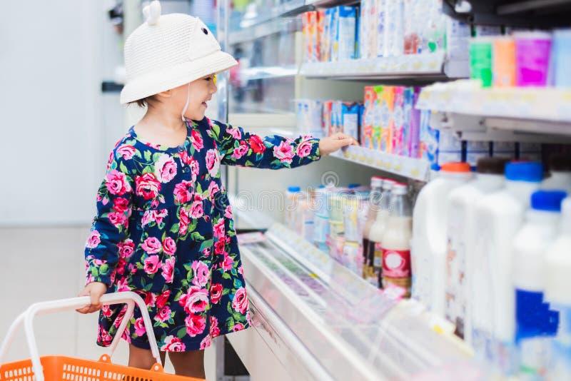 Het zoete Aziatische meisje winkelen in minimarkt met mand, geniet van kopend ding royalty-vrije stock afbeelding