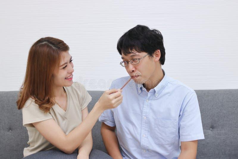 Het zoete en Romaanse jonge Aziatische paar in liefde en heeft geluk in woonkamer royalty-vrije stock afbeeldingen