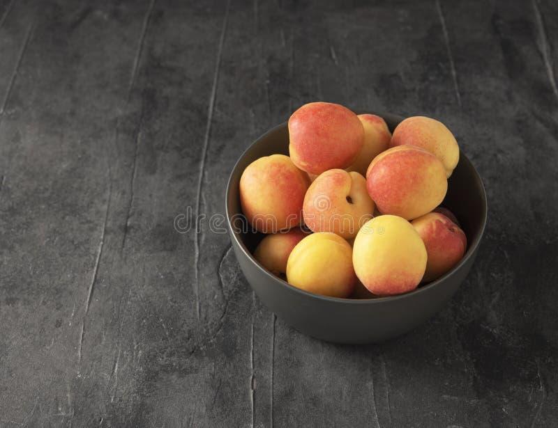 Het zoete heerlijke van de de lijstzomer van de abrikozen donkere kom grijze verse fruit stock fotografie