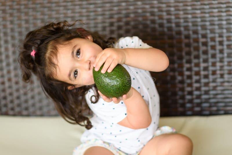 Het zoete kind of het leuke fruit van de de holdingsavocado van het jong geitjemeisje en zit op de laag met ruimte royalty-vrije stock fotografie