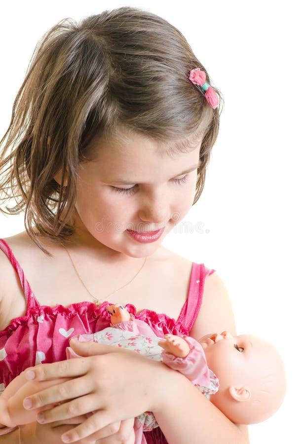 Het zoete meisje die in roze kledingsgreep en het stuk speelgoed van de bedbaby is glimlachen stock afbeeldingen