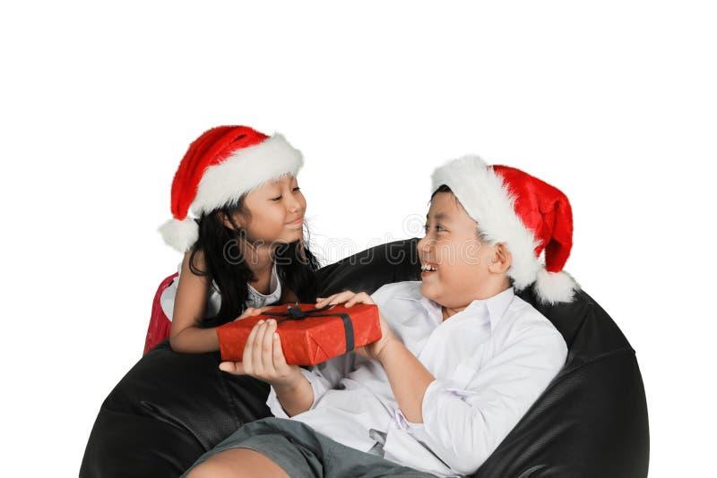 Het zoete meisje geven stelt aan haar broer voor stock afbeelding
