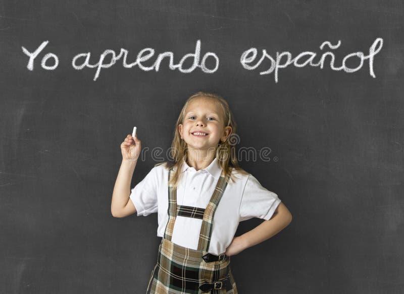 Het zoete ondergeschikte blonde schoolmeisje glimlachen gelukkig in kinderen die Spaans taal en onderwijsconcept leren stock foto