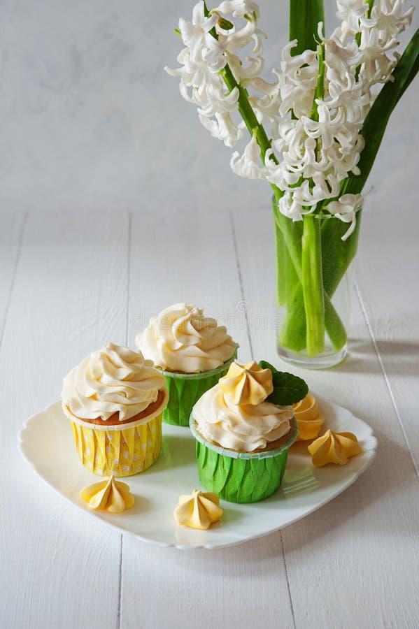 Het zoete romantische ontbijt met bloemen van de boeket de verse lente, defocused de houten achtergrond van het vanille capcake d stock afbeelding