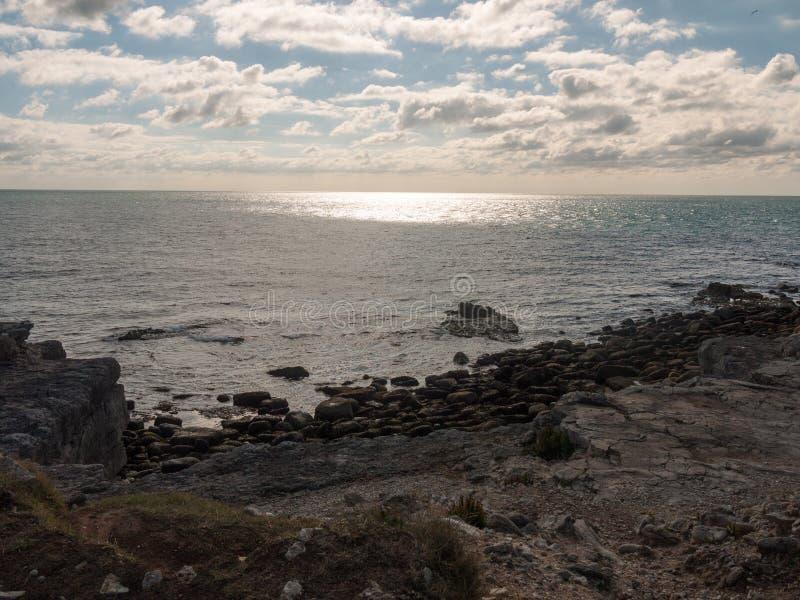 het zonlicht door wolken over Jura oceaanaardlandschap is royalty-vrije stock afbeeldingen