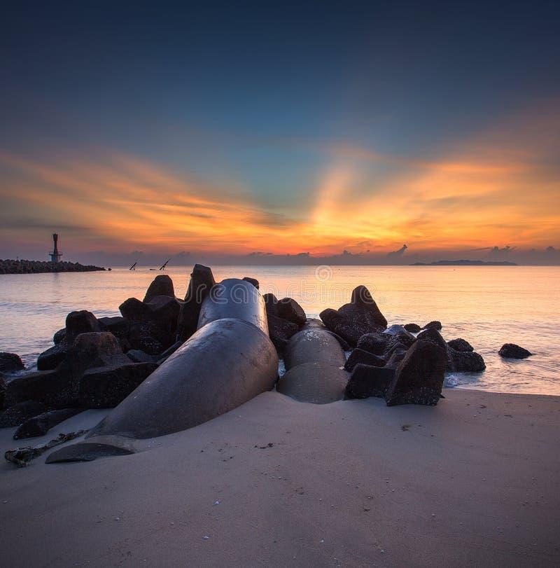 Het zonlicht doordringt de wolken om tot humeurige verlichting op een visserijpijler bij schemer te leiden stock foto's