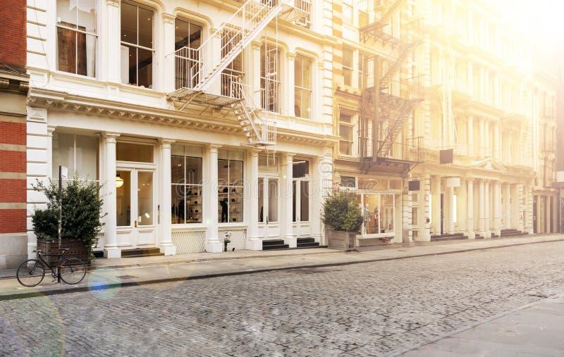 Het zonlicht glanst op de lege stoepen langs kei behandelde Greene-Straat in de SoHo-buurt van Manhattan in New York stock fotografie