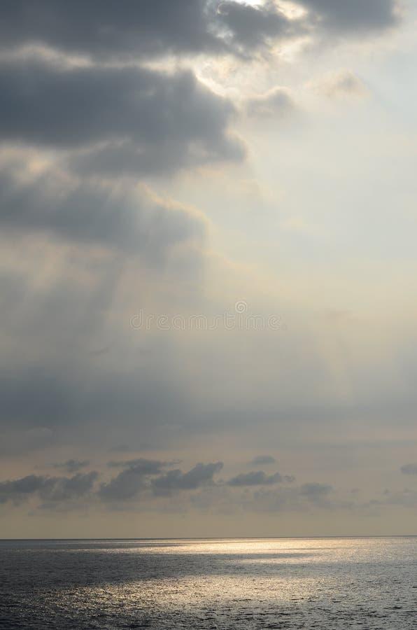 Het zonlicht glanst op overzees dichtbij avond stock foto