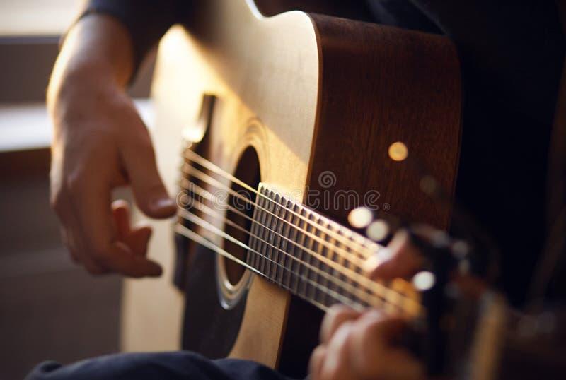 Het zonlicht verlicht de gitarist, die een melodie op een gitaar spelen stock foto's