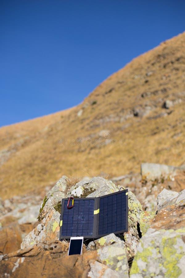 Het zonnepaneel aan de tent wordt verbonden die De mensenzitting naast mobiele telefoonlasten van de zon stock afbeeldingen