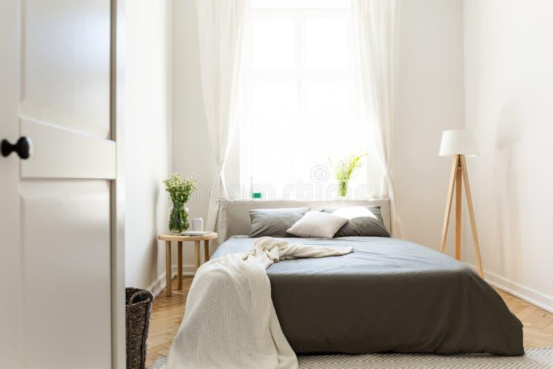 Het zonnige natuurlijke binnenland van de stijlslaapkamer met een bed in het midden, grijze linnen en de hoofdkussens, en een van stock fotografie