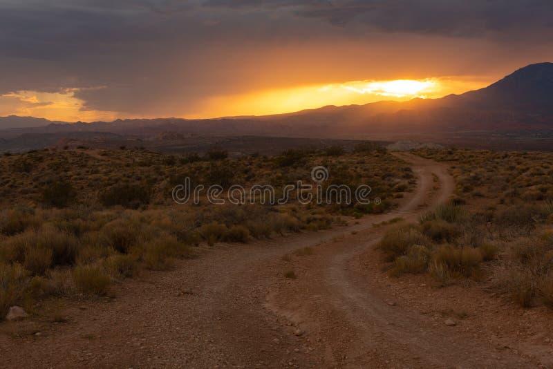Het zonsonderganglicht gloeit sinaasappel over een landschap met een landweg die in de woestijn met de zon leiden die achter wolk royalty-vrije stock fotografie