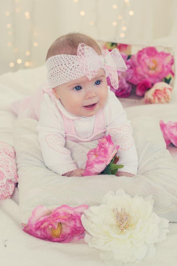 Het zuigelingsmeisje ligt op bed met roze bloemen stock foto's