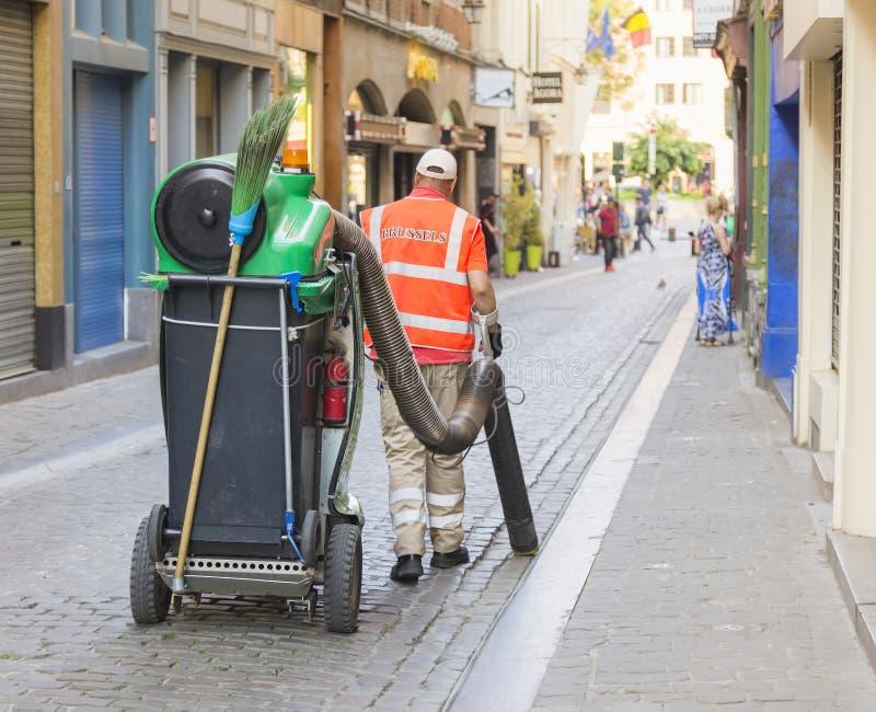 Het zuigen met een grote stofzuiger op een stadsstraat stock foto