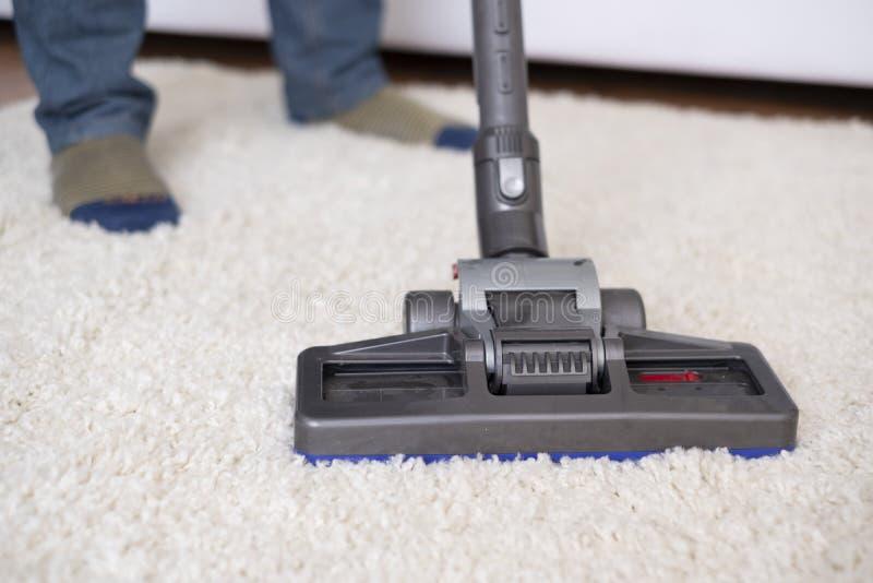 Het zuigen van wit tapijt die de stofzuiger met behulp van royalty-vrije stock afbeeldingen