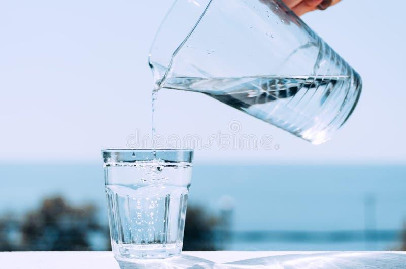 Het zuivere water van een kruik wordt gegoten in een glasbeker Glas met water op de achtergrond van het overzees stock foto