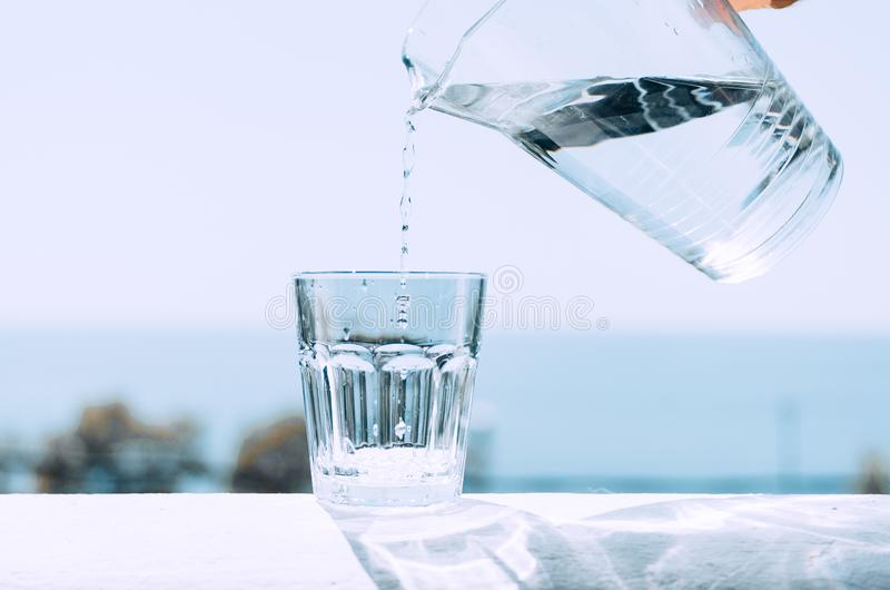 Het zuivere water van een kruik wordt gegoten in een glasbeker Glas met water op de achtergrond van het overzees royalty-vrije stock foto