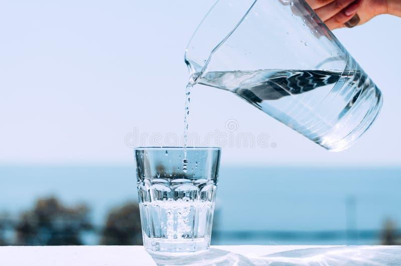 Het zuivere water van een kruik wordt gegoten in een glasbeker Glas met water op de achtergrond van het overzees royalty-vrije stock afbeeldingen