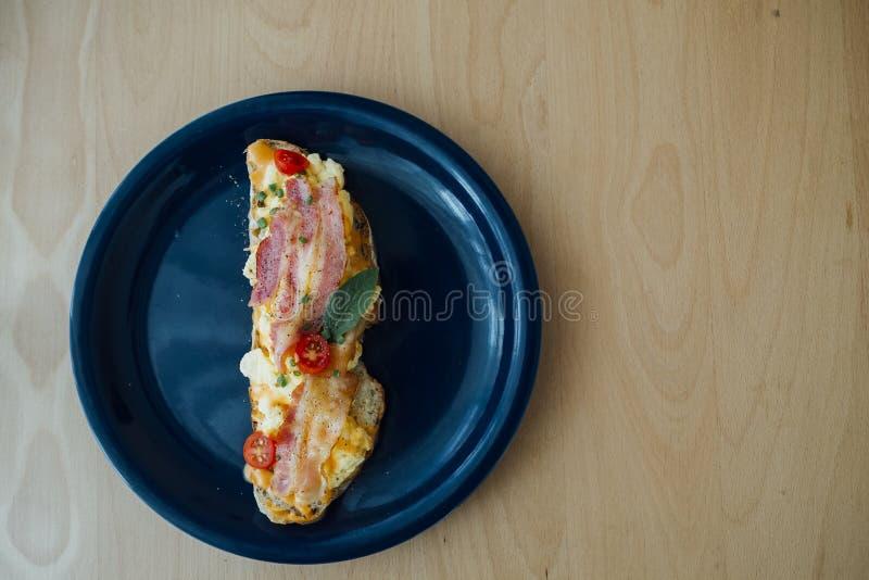 Het zuurdesembrood met bacon wordt bedekt en gooit eieren dat door elkaar stock fotografie