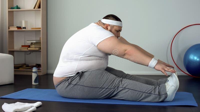 Het zwaarlijvige mannelijke uitrekken zich op mat na huistraining, spiertoon, lichaamsflexibiliteit royalty-vrije stock foto