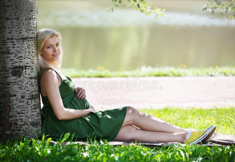 Het zwangere blondemeisje zit onder een boom in het park stock foto