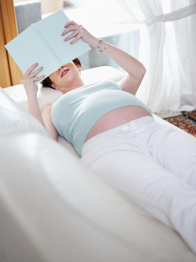 Het zwangere boek van de vrouwenlezing thuis stock foto