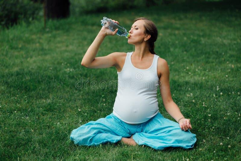 Het zwangere drinkwater van de yogavrouw van een fles, in de lotusbloempositie park, gras, openlucht, bos stock afbeelding