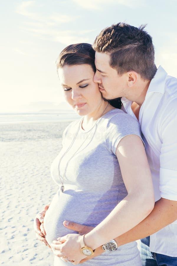Het zwangere jonge paar op elkaar inwerken, die zich in openlucht bevinden royalty-vrije stock fotografie